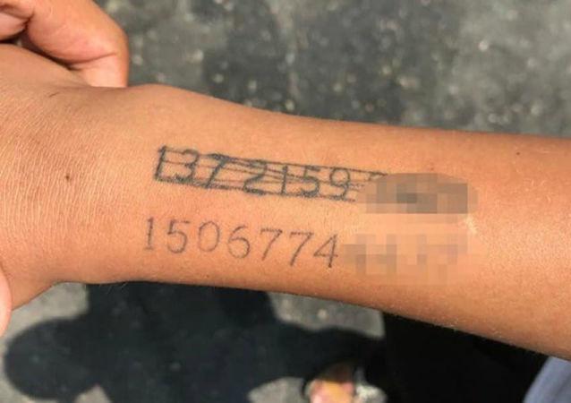 tetování s telefonním číslem matky na zápěstí čínského chlapce