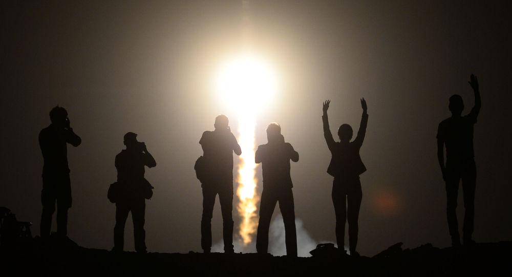 Lidé sledují vypouštění nosné rakety Sojuz-FG s pilotážní lodí Sojuz TMA-13M a posádkou 40.-41. expedicí na MKS z kosmodromu Bajkonur.