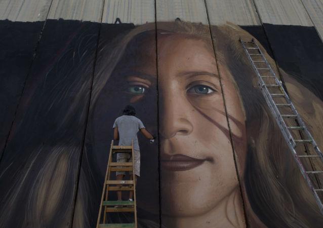 Graffiti palestinské vězenkyně Ahed Tamimi na stěně u Betléma