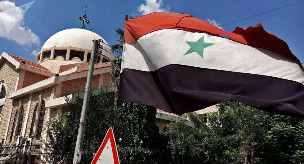 Syrská vlajka před pravoslavným kostelem v křesťanské čtvrti v Aleppu