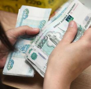 Pracovnice přepočítává peníze. Ilustrační foto