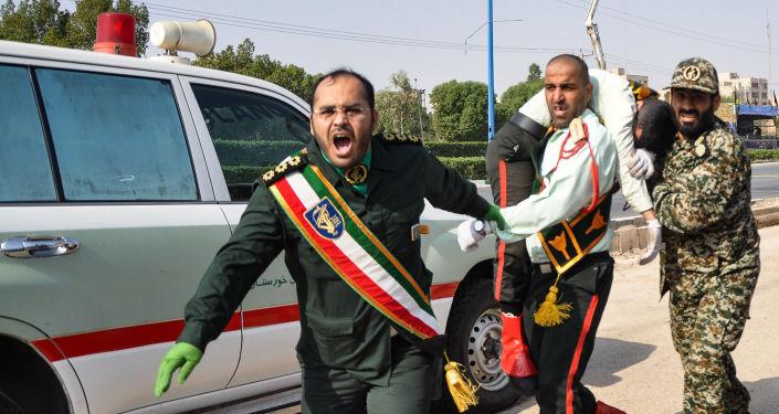 Účastníci vojenské přehlídky v íránském městě Ahváz odnášejí zraněného v důsledku teroristického útoku.