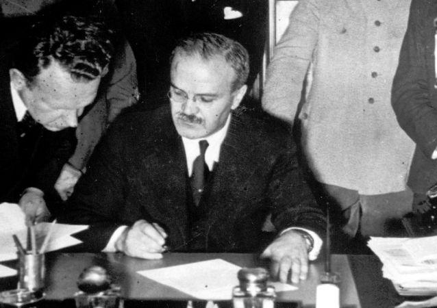 Sovětský vůdce Josif Stalin sleduje jak ministr zahraničí SSST Vjačeslav Molotov a ministr zahraničí nacistického Německa Joachim von Ribbentrop podepisují pakt o neútočení.
