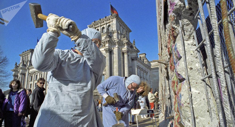 Obyvatelé NDR rozebírají Berlínskou zeď. 1990