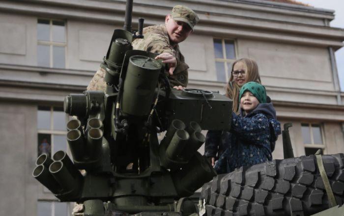 Americký voják ukazuje dětem obrněné vozidlo Stryker v Praze