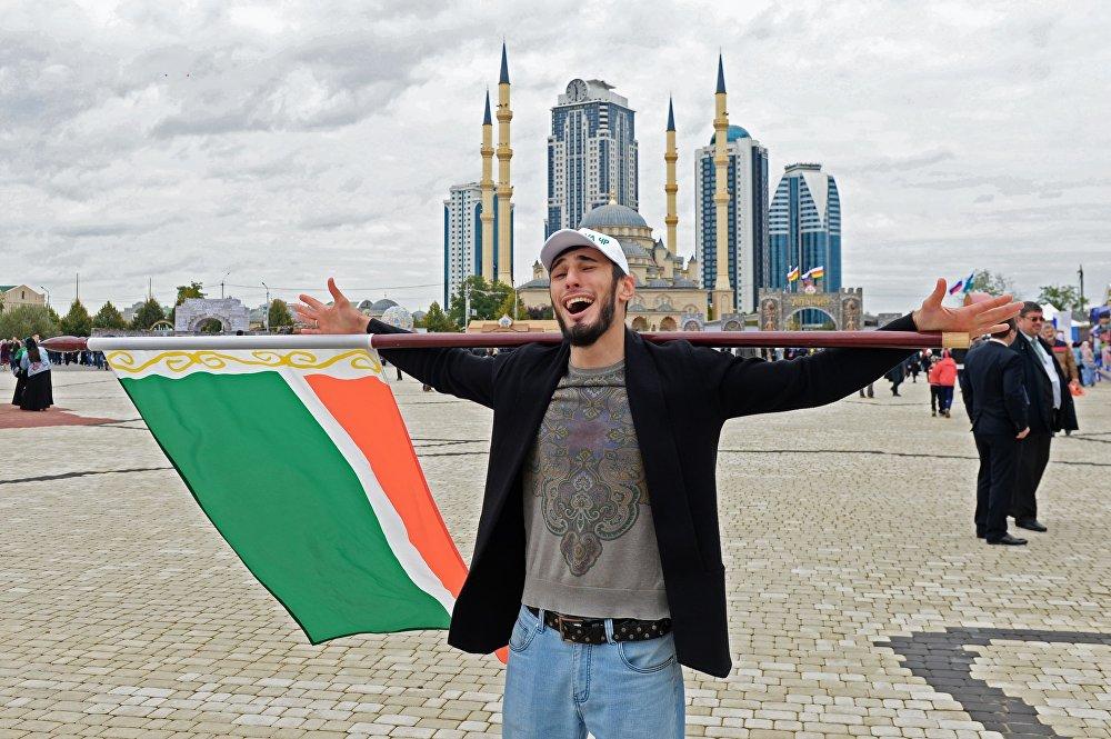 Muž s vlajkou Čečenské republiky na náměstí Achmata Kadyrova během oslav 200. výročí města Grozný.