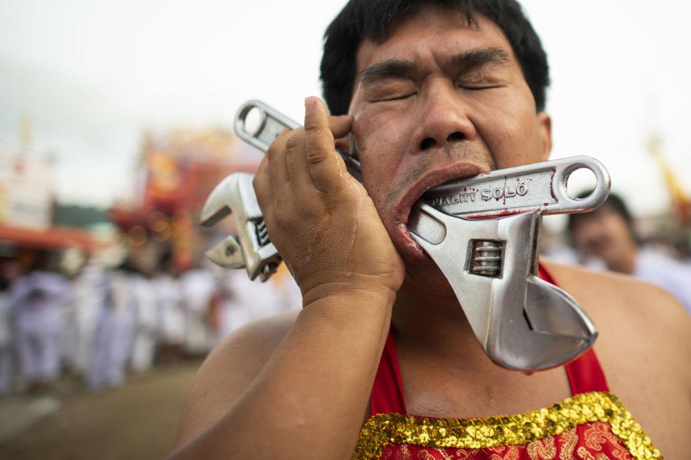 Jeden z příznivců svatyně Loem Hu Thai Su, který má v obličeji francouzský klíč.