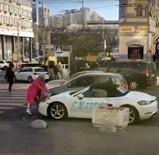 V centru Kyjeva oslnivá blondýna rozbila sekerou Porsche (VIDEO)