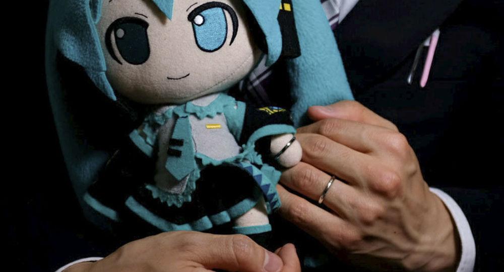 Japonec Akihiko Kondo pózuje s panenkou, znázorňující hologram jeho manželky - virtuální zpěvačky Hatsune Miku