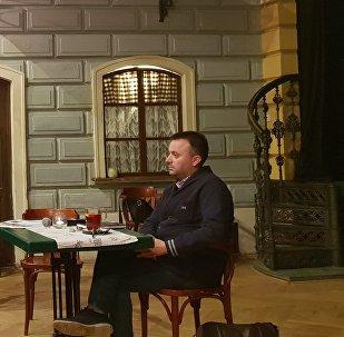Moderátor představuje novináře Ondřeje Kundru, který sedí u stolu a čeká na slovo