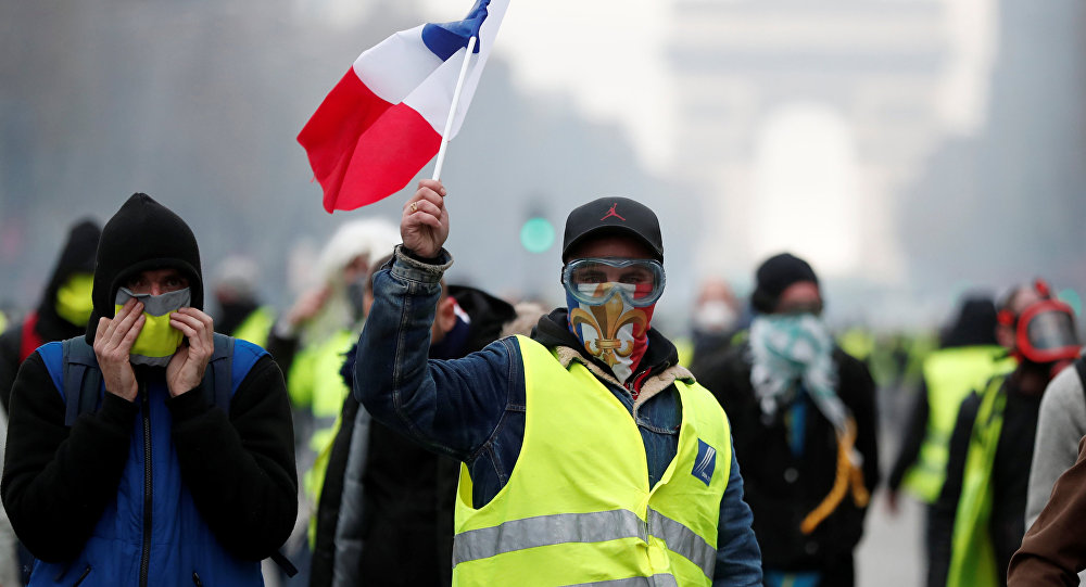 Masked protesters wearing yellow vests, a symbol of a French drivers' protest against higher fuel prices, take part in a demonstration on the Champs-Elysees in Paris, France, November 24, 2018