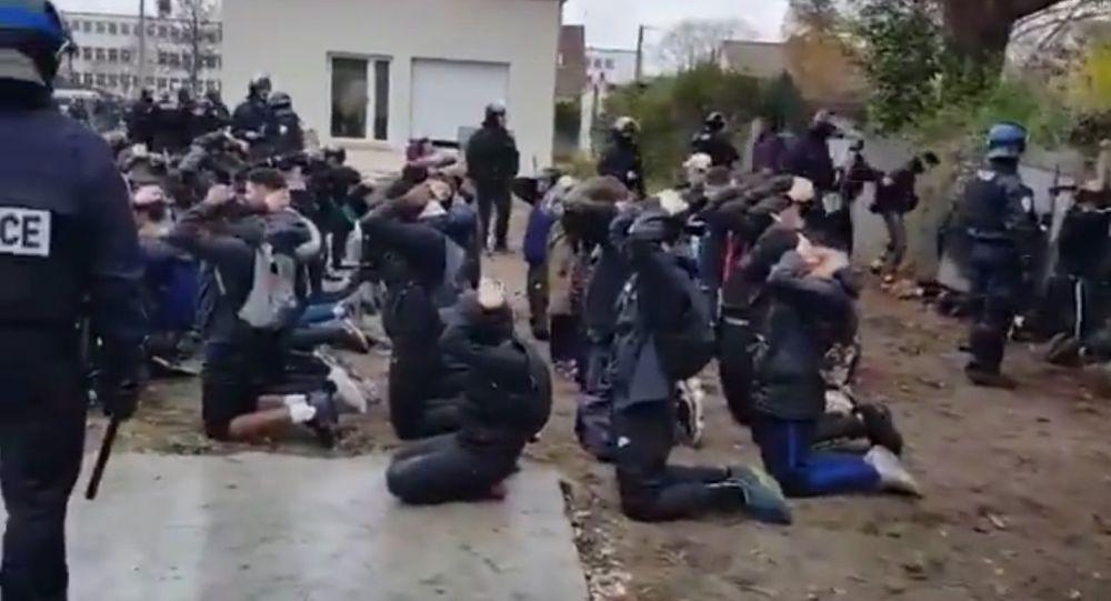 Francouzští studenti na kolenou s rukama za hlavou