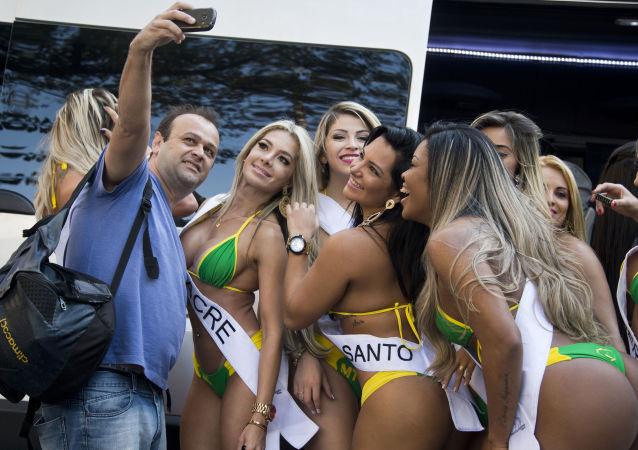 Muž dělá selfie s účastnicemi soutěže Miss Brazílie 2015