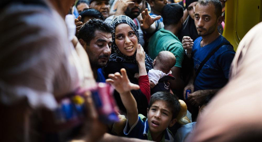 Migranti čekající na výdej jídla od makedonských dobrovolníků na železniční stanici Gevgelija na makedonsko-řecké hranici