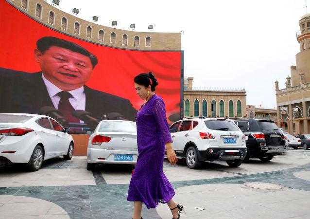Ujgurka prochází kolem velké obrazovky s čínským prezidentem Si Ťin-pchingem na náměstí v Kašgar v Ujgurské autonomní oblasti Sin-ťiang.