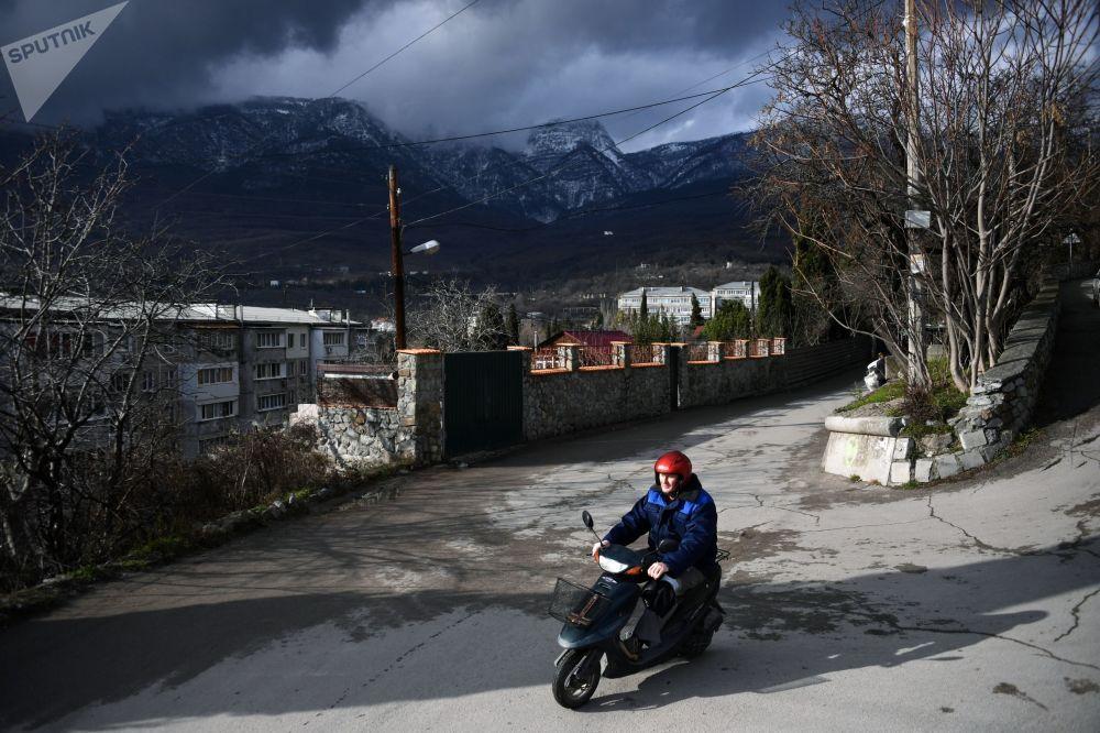 Muž jede na mopedu v Gurzufu na Krymu