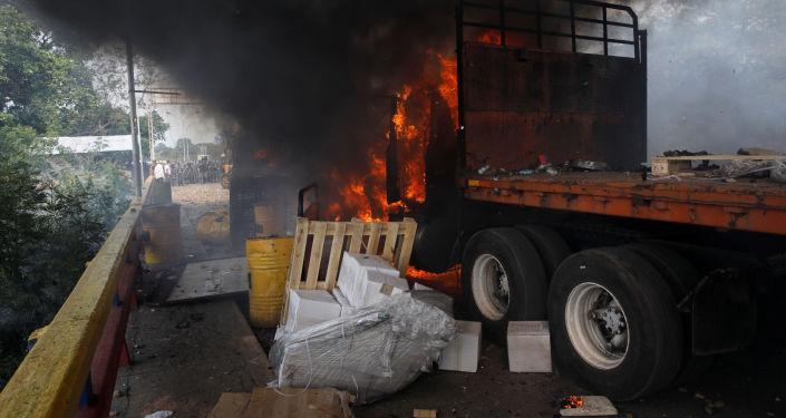 Hořící nákladní auto s humanitární pomocí pro Venezuelu na hranici s Kolumbií