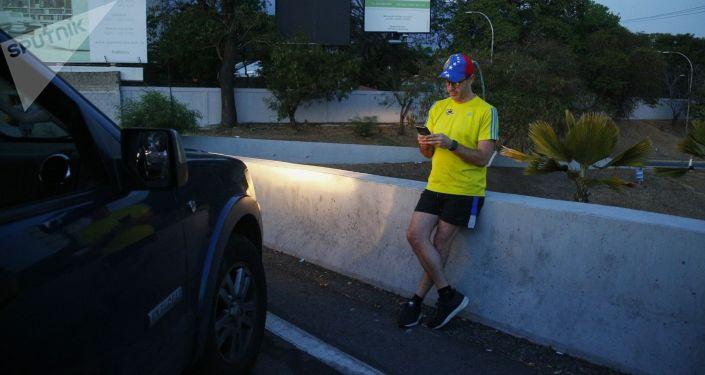 Občan Caracasu se snaží chytit mobilní signál.
