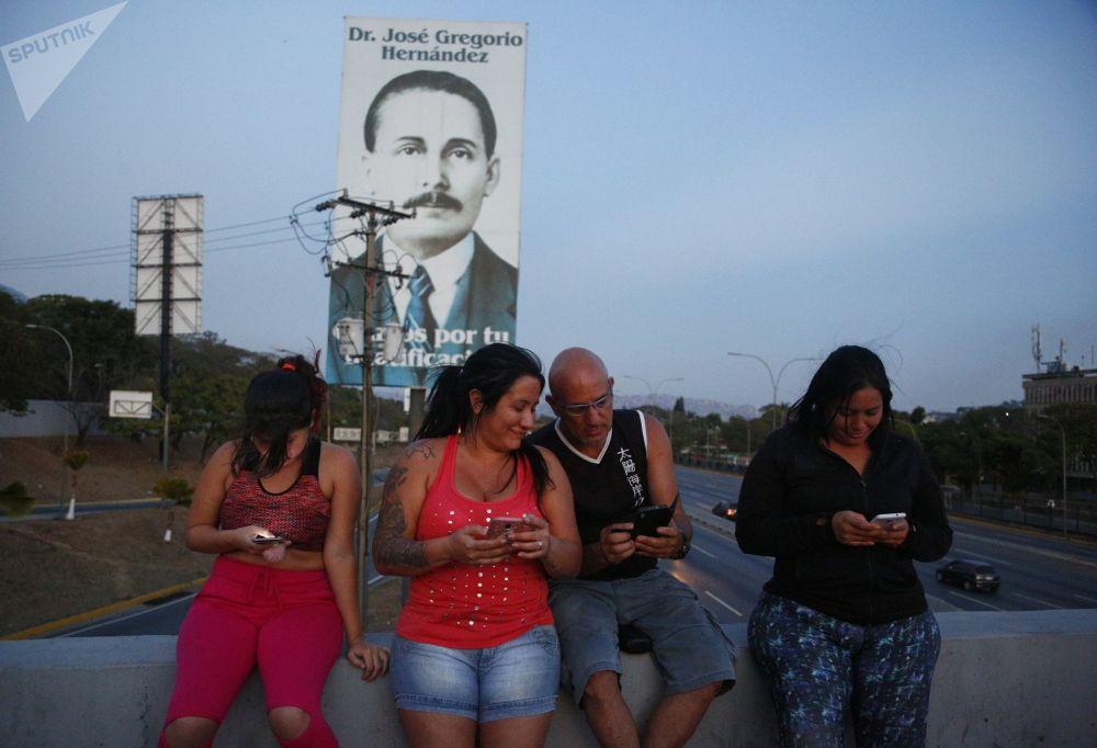 Lidé se snaží chytit mobilní signál na dálnici v Caracasu