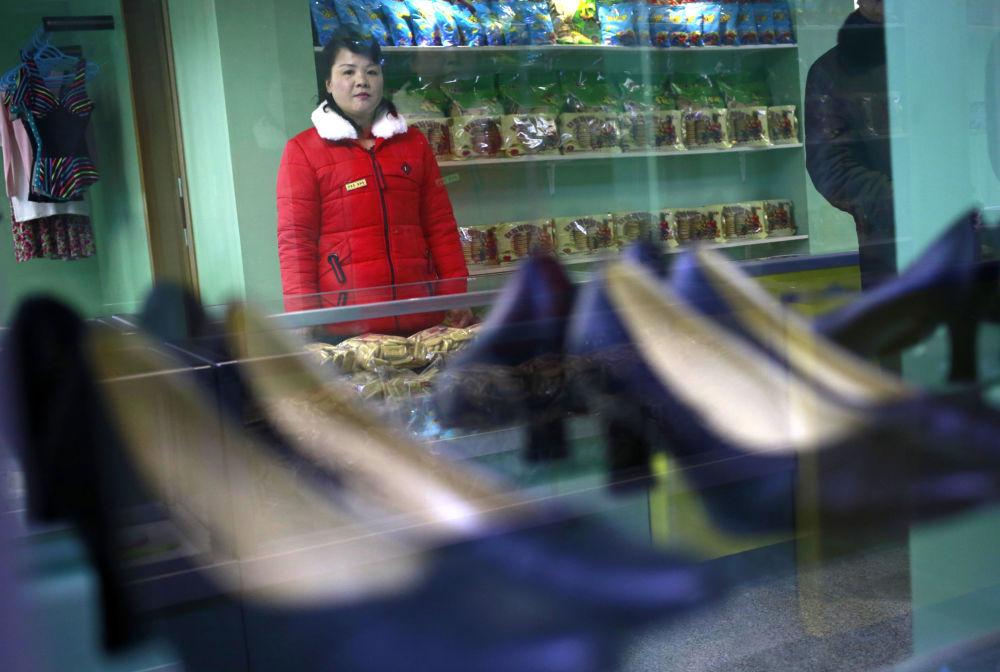 Žena ve službě, která stojí u obchodu nedaleko ubytovny jedné textilní továrny v Pchjongjangu, KLDR.