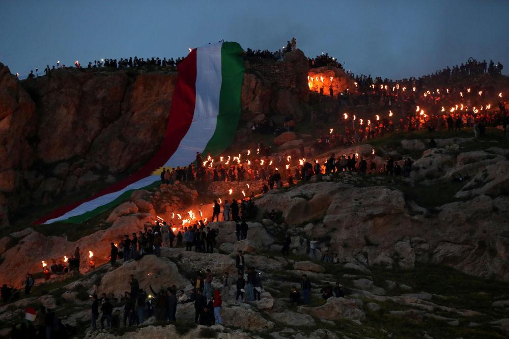 Iráčtí Kurdové během oslav Nourúza nesou pochodně na horu.