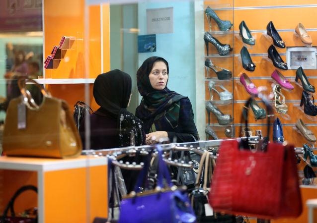 Žena si kupuje obuv v íránském obchodním centru