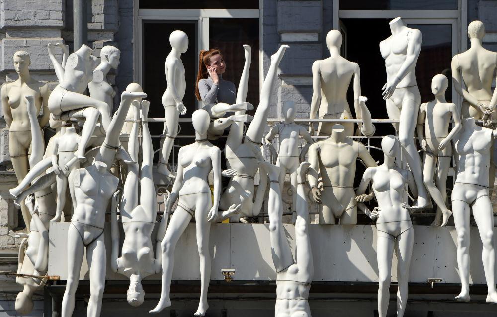 Žena mluví po telefonu na balkóně vedle figurín v Kyjevě, Ukrajina