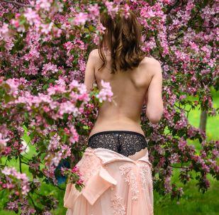 Modelka pózuje ve višňovém sadu v Moskvě.