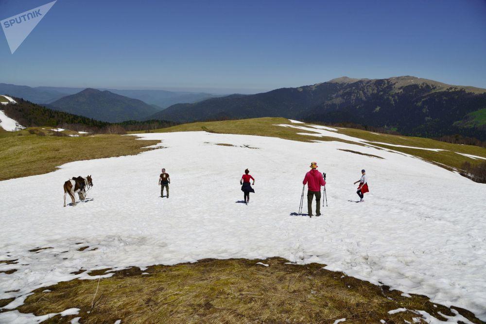 Turisté na zasněžené pastvině Abago v severní oblasti Kavkazské chráněné krajinné oblasti.