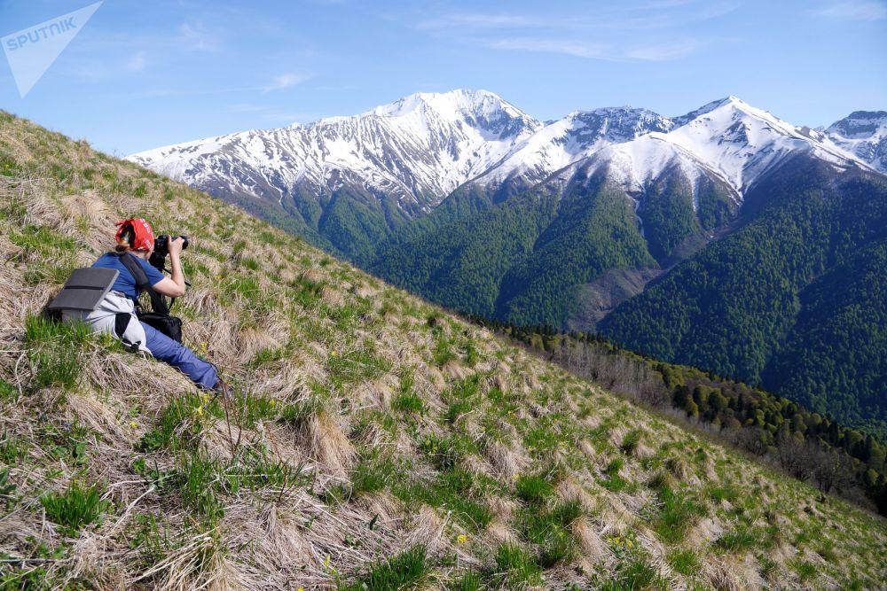 Dívka fotí krajinu Kavkazské přírodní biosférické rezervace Ch. G. Šapošnikova.