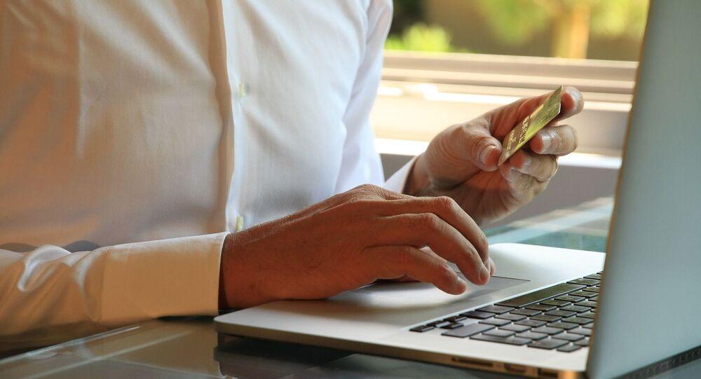 Muž s platební kartou u počítače
