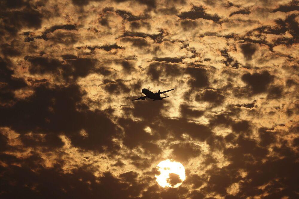 Silueta letadla na pozadí plápolajících mraků během západu slunce v Ahmadábádu, Indie