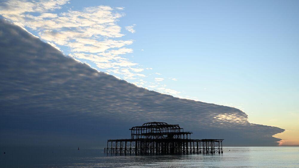 Mraky připomínající obrovskou vlnu nad pláží v Brightonu na jihu Anglie