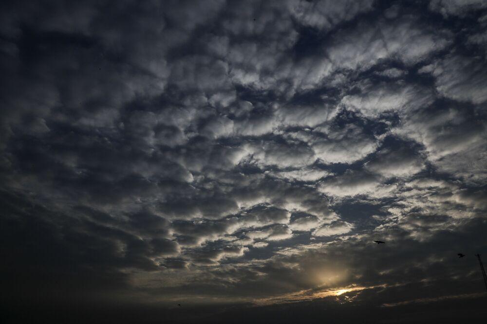 Barchany z mraků při západu slunce nad indickou Kalkatou během cyklónu