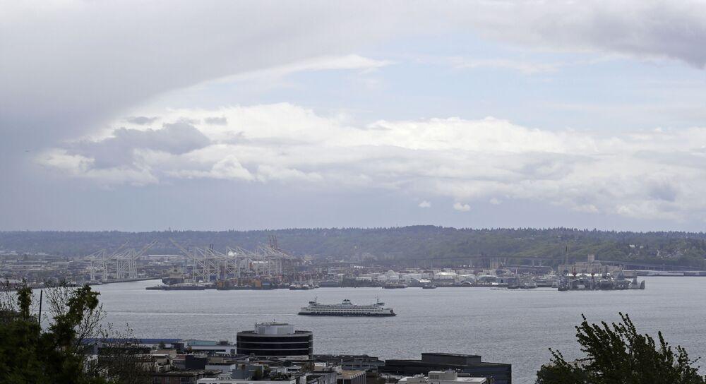 Mraky připomínající polokouli Země nad trajektem opouštějícím přístav, Seattle