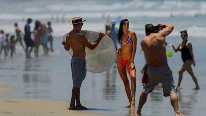 Dívka pózuje pro fotografa na pláži v San Diegu, USA