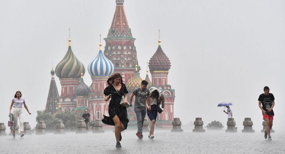 Lidé na Rudém náměstí během silného lijáku v Moskvě