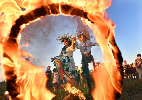 Dívka a mladík skáčou přes oheň na festivalu Ivana Kupaly v Turově, Bělorusko - Sputnik Česká republika