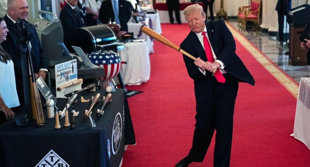 Americký prezident Donald Trump mává baseballovou holí v Bílém domě