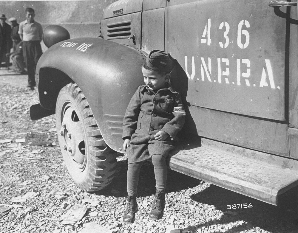 Čtyřletý bývalý vězeň tábora Buchenwald poblíž auta UNRRA, r. 1945.