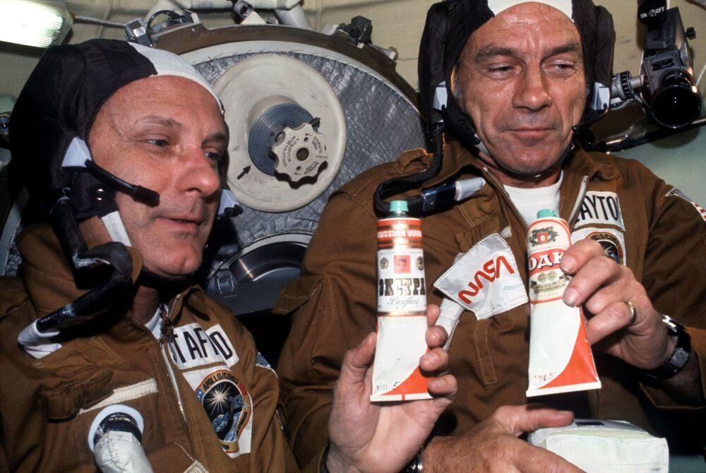 Astronauti Thomas Patten Stafford a Donald Kent Slayton s tubičkami boršče a vodky poté, co došlo ke spojení lodí Sojuz-Apollo ve vesmíru.