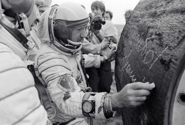 Sovětský kosmonaut Alexej Leonov píše poděkování všem účastníkům programu Sojuz-Apollo (EPAS) na palubě spuštěného přístroje. - Sputnik Česká republika
