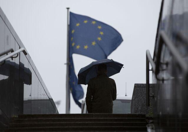 Muž prochází kolem sídla EU v Bruselu
