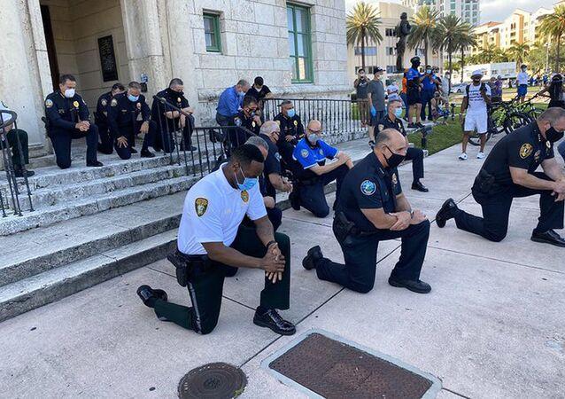 Američtí policisté v Miami klečí před demonstranty