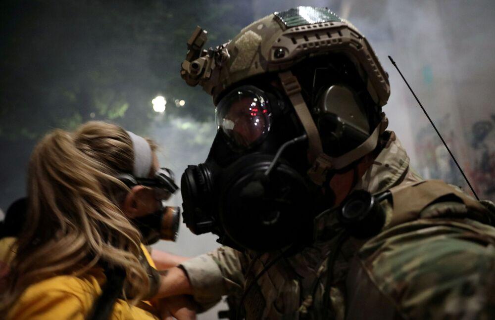 Policejní důstojník odstrkuje ženu během protestu v americkém Portlandu, stát Oregon.