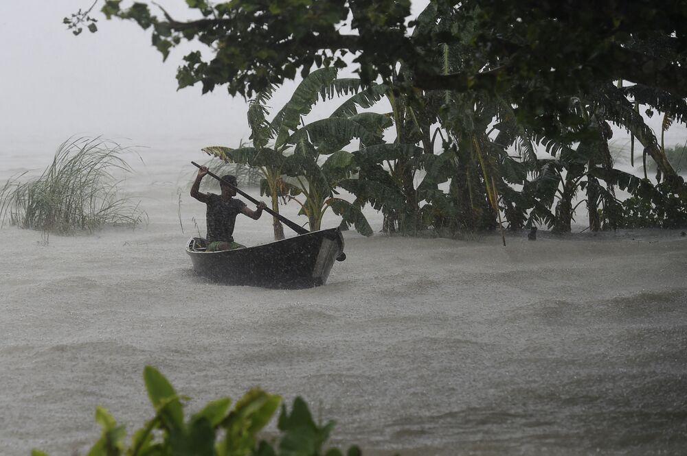 Muž v lodi během povodně v Doharu, Bangladéš.