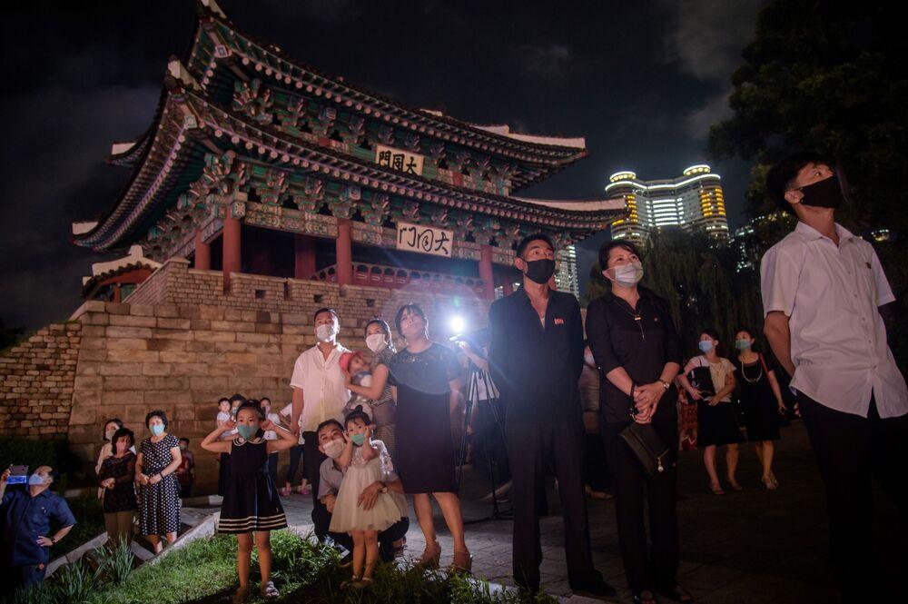 Lidé se dívají na ohňostroj na počest výročí podpisu Dohody o neútočení na Korejském poloostrově. Pchjongjang, KLDR.