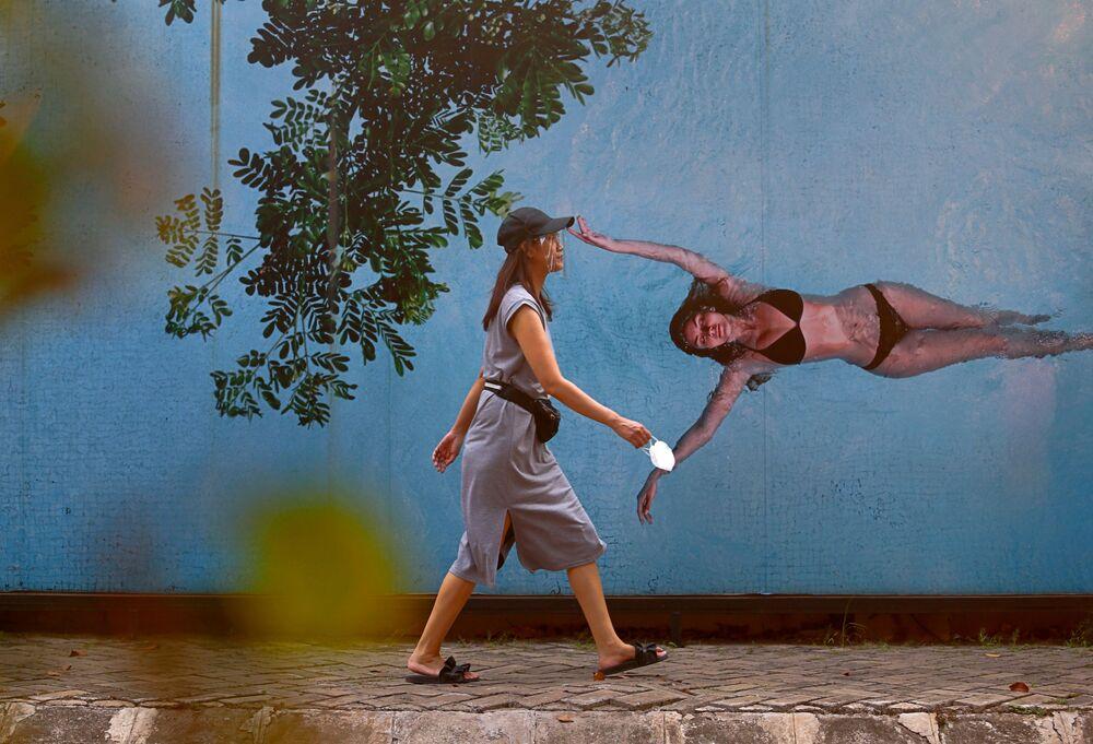 Žena s ochranným štítem proti koronaviru v Jakartě, hlavním městě Indonésie.