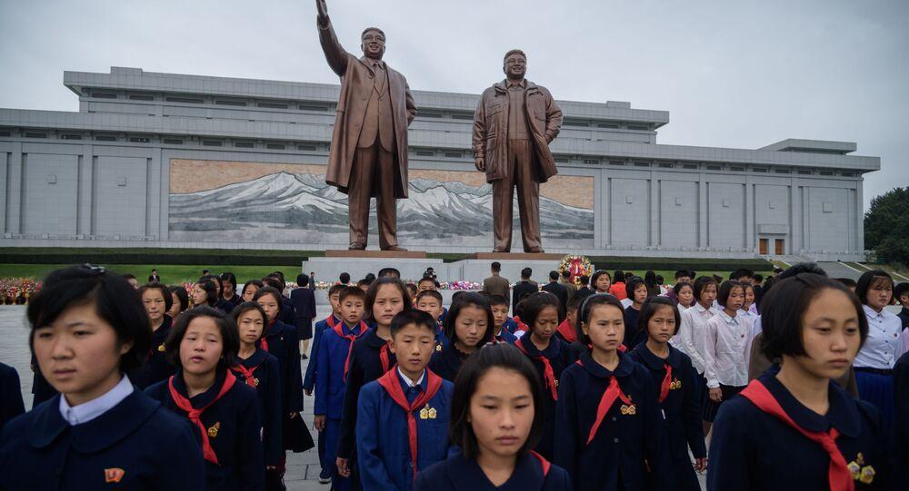 Studenti před sochami severokorejských vůdců Kim Il Sung a Kim Jong Il