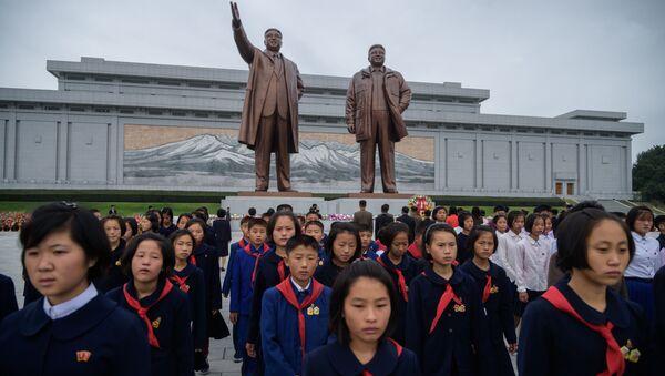 Studenti před sochami severokorejských vůdců Kim Il Sung a Kim Jong Il - Sputnik Česká republika